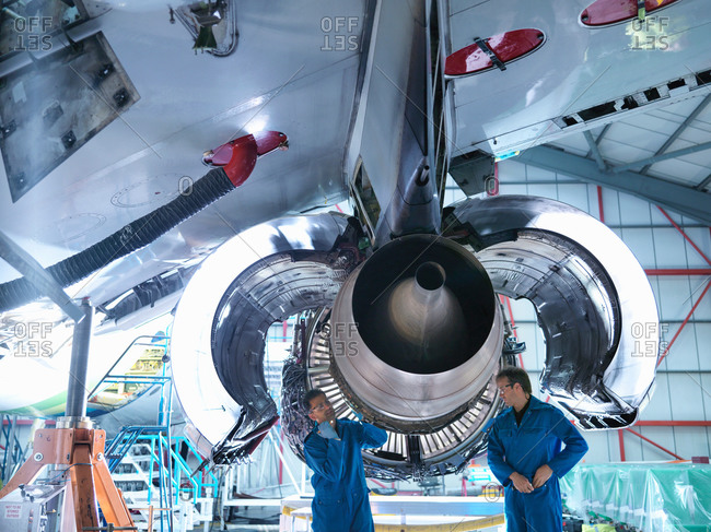 Two engineers working on jet engine in aircraft maintenance factory