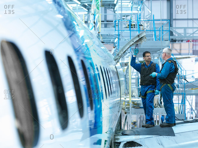 Engineers in discussion on  aircraft wing in aircraft maintenance factory