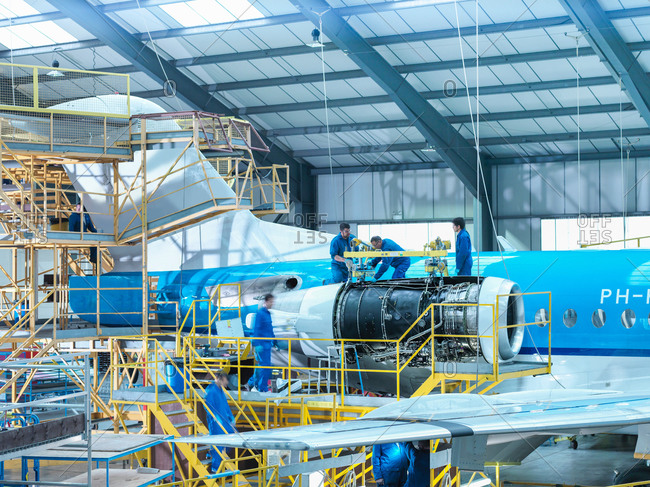 Group of engineers removing jet engine from aircraft in aircraft maintenance factory