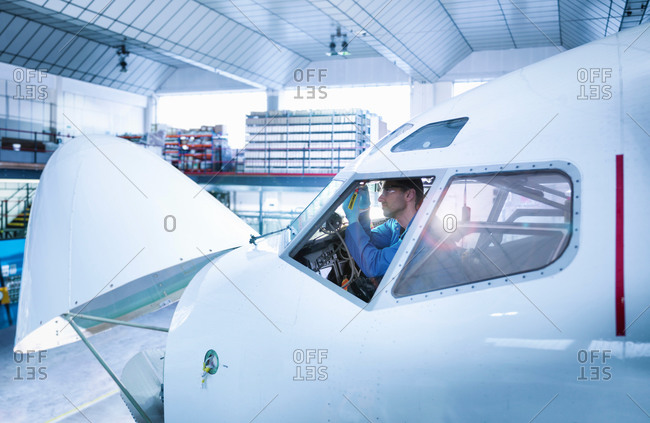 Engineer working in aircraft cockpit in aircraft maintenance factory