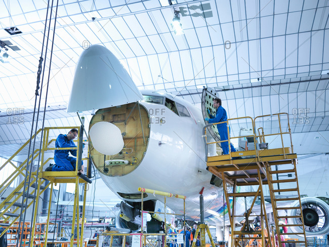 Two engineers working on aircraft in aircraft maintenance factory