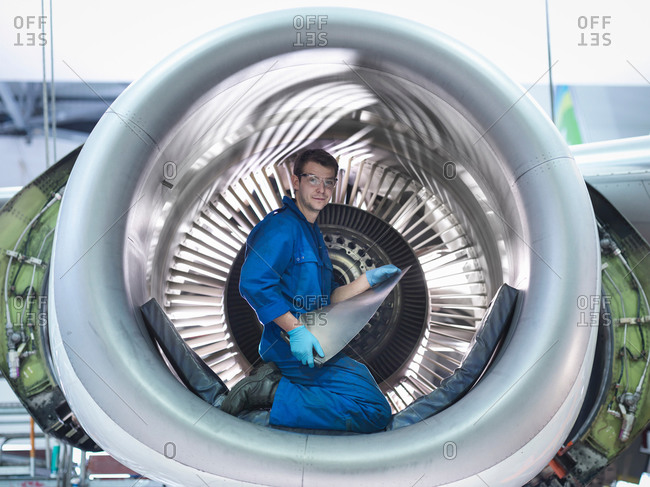 Portrait of an engineer holding jet engine turbine blade in aircraft maintenance factory