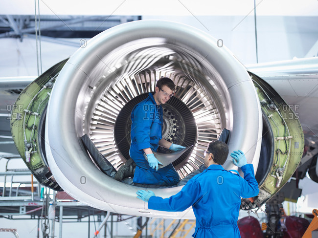 Engineers working with jet engine turbine blade in aircraft maintenance factory
