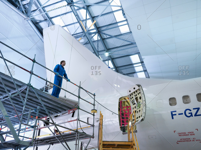 Engineer on scaffolding by aircraft in aircraft maintenance factory, low angle view