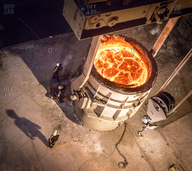 High angle view steel workers inspecting molten steel in flask