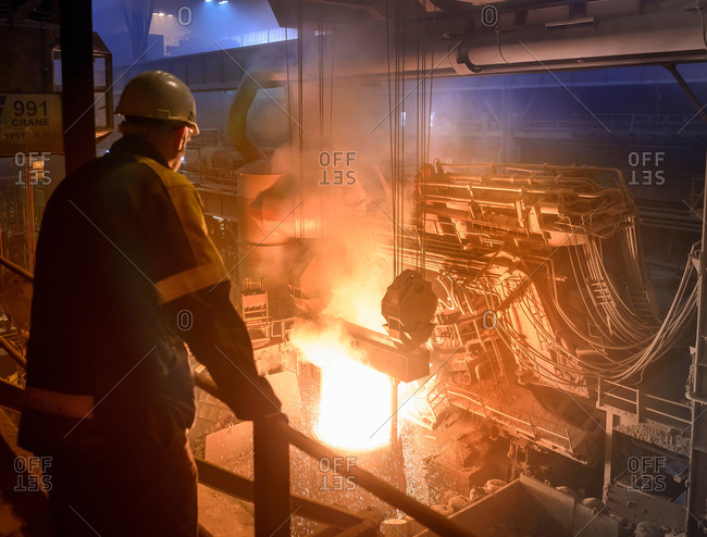 Steel worker inspecting pouring molten steel