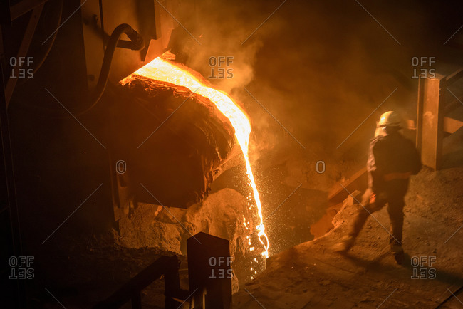 Steel worker inspecting pouring molten steel, high angle view