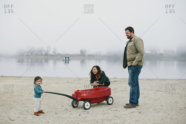 Little girl pulling red wagon with parents next to lake