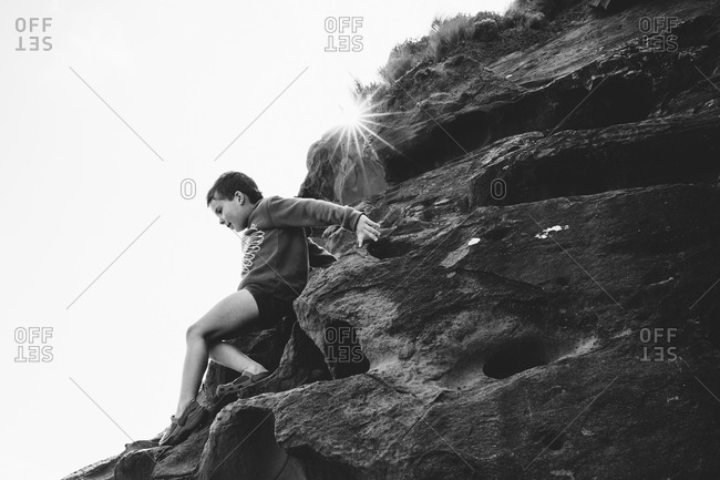 Boy climbing down the side of a steep rocky hill