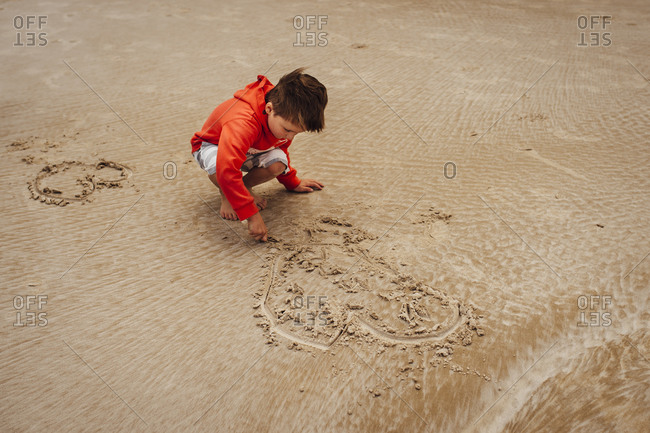 Boy drawing in the sand on the beach