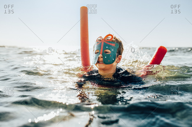 Boy wearing mask swimming in the ocean with a noodle