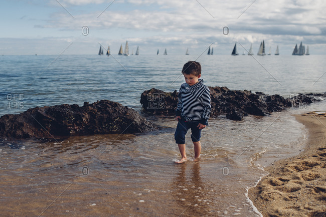 Little boy walking along the shore with sailboats in the distance