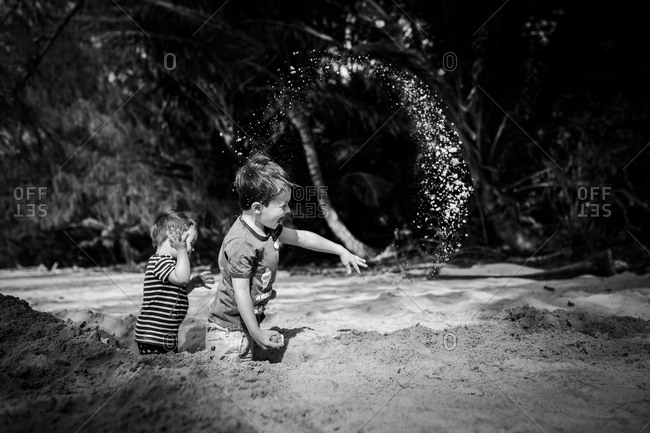 Two boys throwing sand