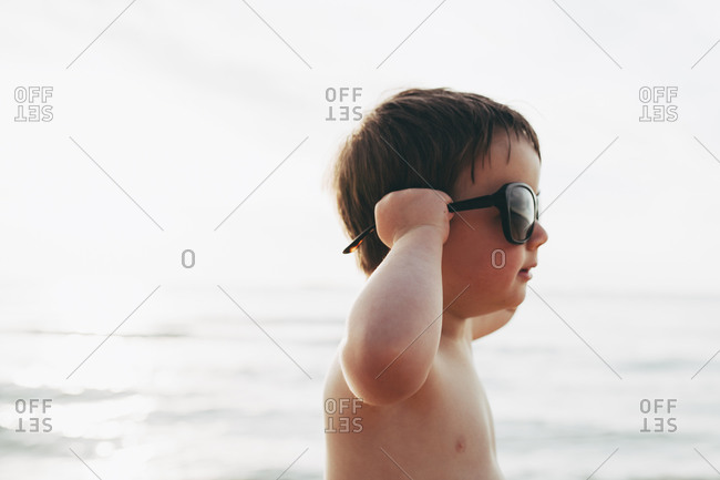 Little boy trying on a large pair of sunglasses