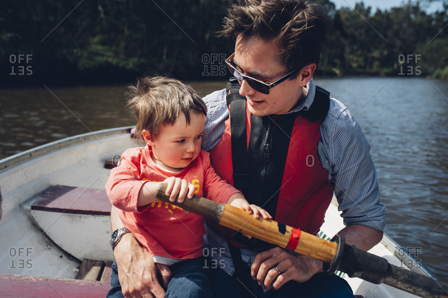Father holding toddler a row boat