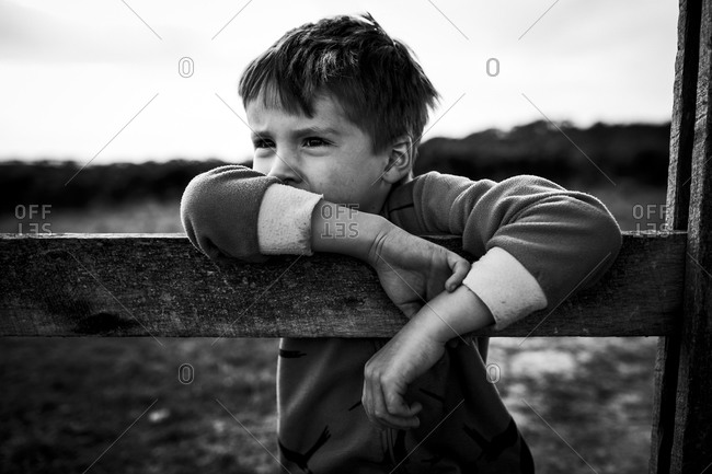 Boy leaning on a fence