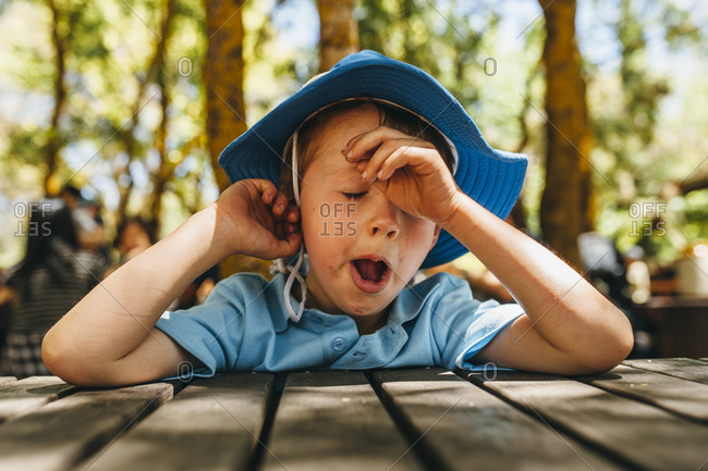 Boy wearing blue hat yawning