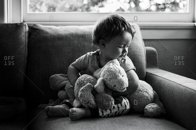 Baby boy sitting on sofa with stuffed animals