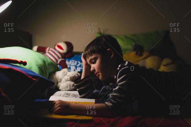 Boy reading on bed at night