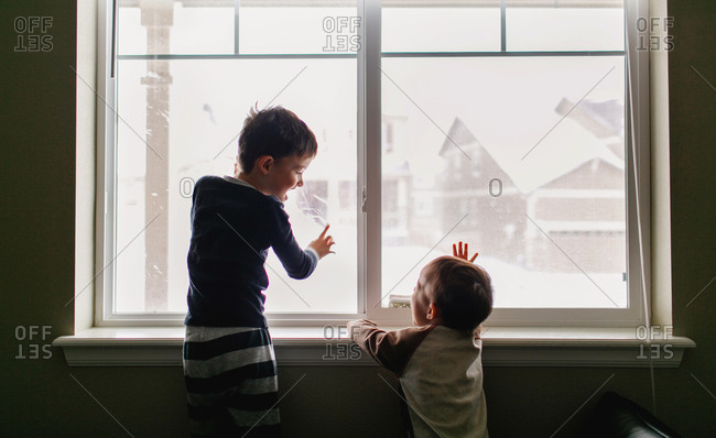 Boy and toddler laughing by window