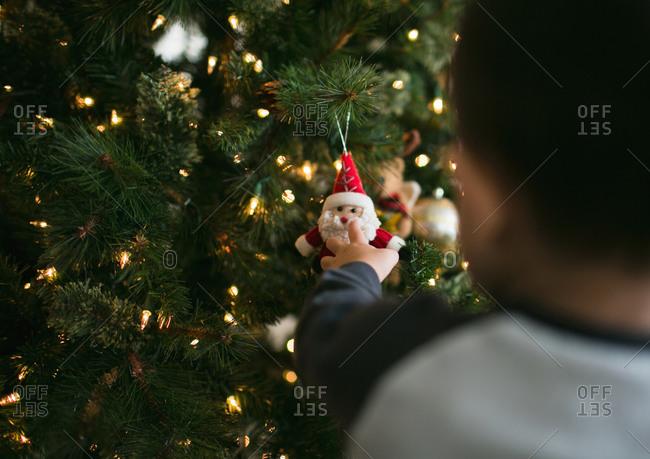 Boy touching Christmas ornament