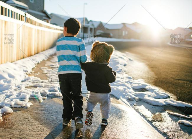 Boys walking in snowy suburb