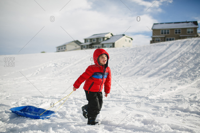 Boy pulling sled in subdivision