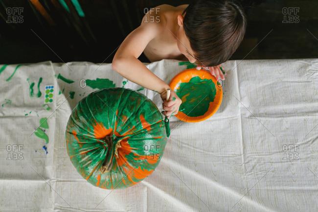 Boy painting a pumpkin