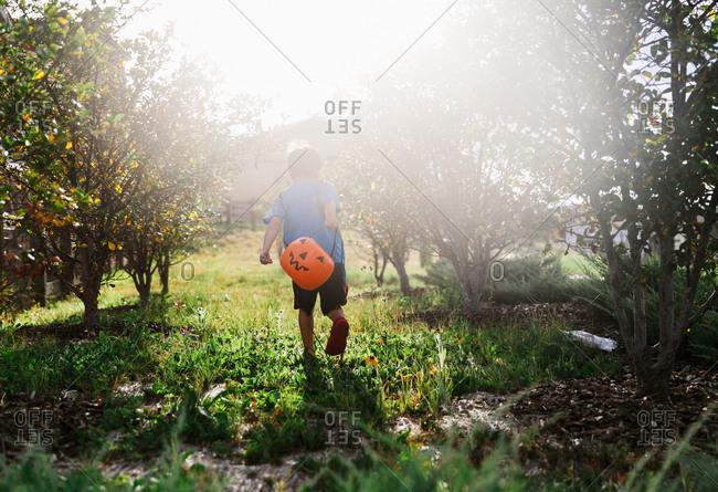Boy outside with pumpkin bucket