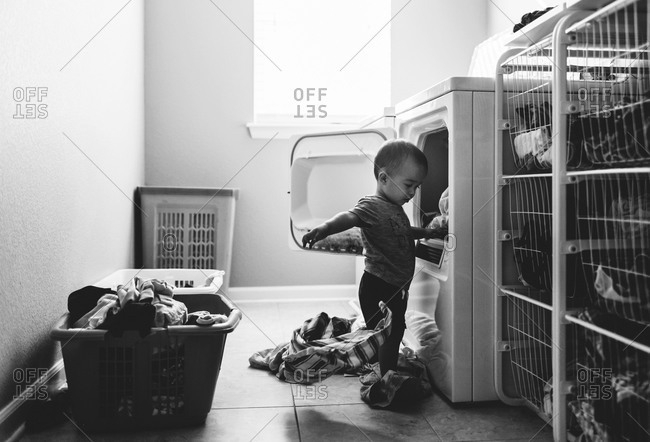 Toddler pulling laundry from dryer