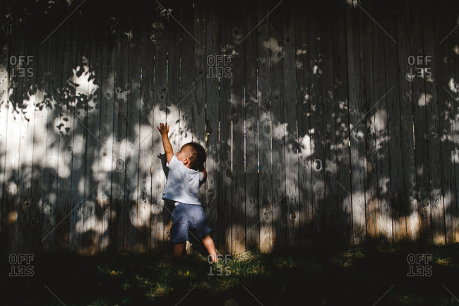 Boy reaching for shadow on fence
