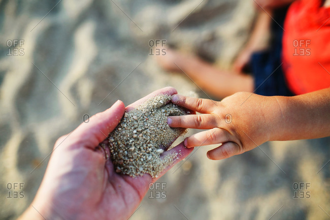 Child touching sand in adult's hand