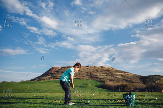 Boy playing golf on course