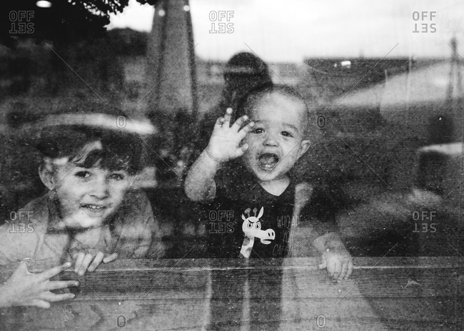Boys looking out reflective window