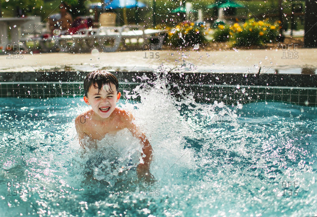 Laughing boy jumping into pool