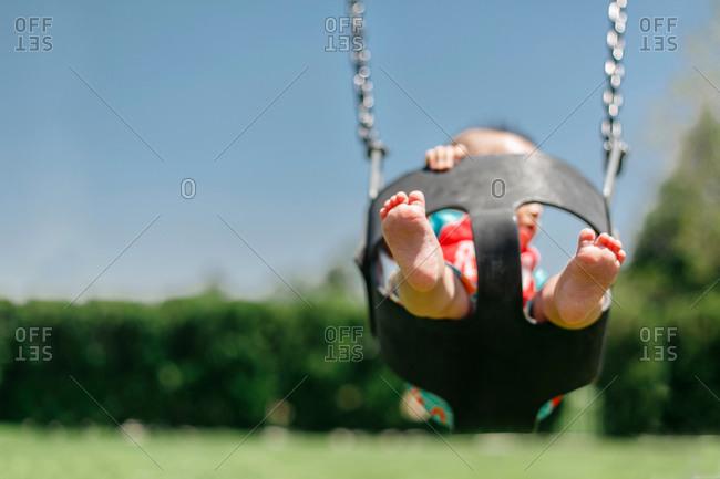Barefoot toddler in playground swing