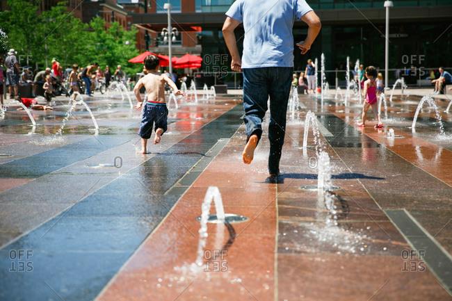 Boy and man running through fountain