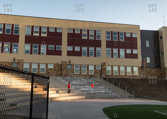 Boy on steps in schoolyard