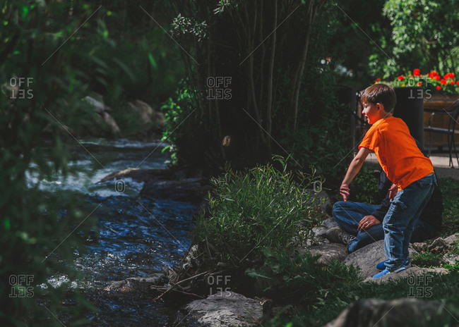 Boy throwing rock in rural stream