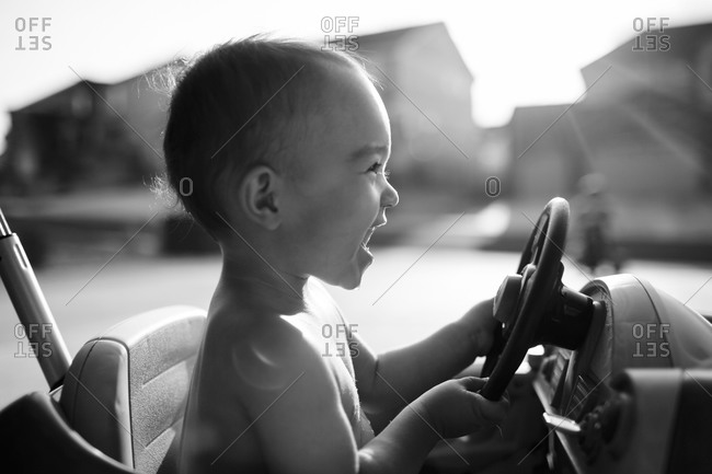 Smiling boy in toy car