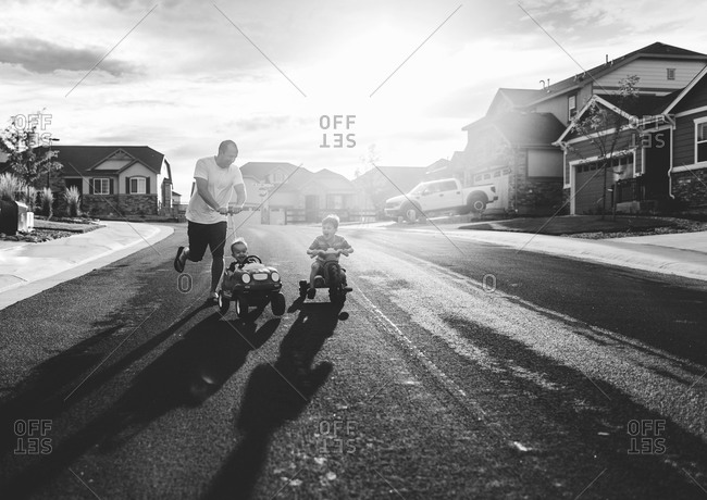 Man pushing boys in wheeled toys