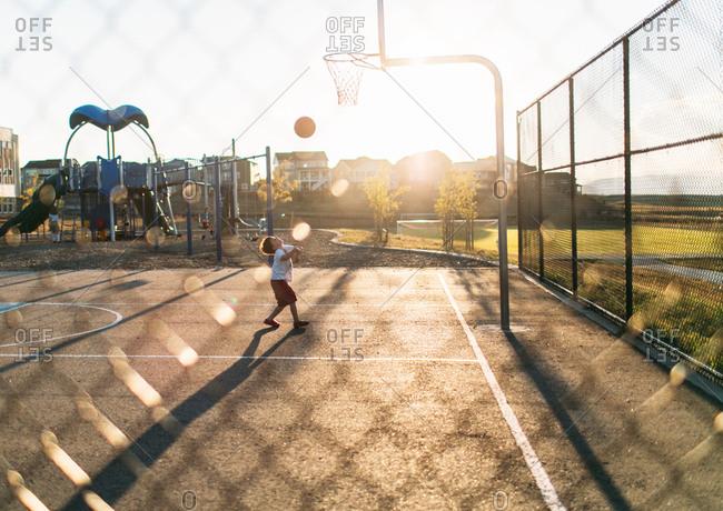 Boy throwing basketball to hoop
