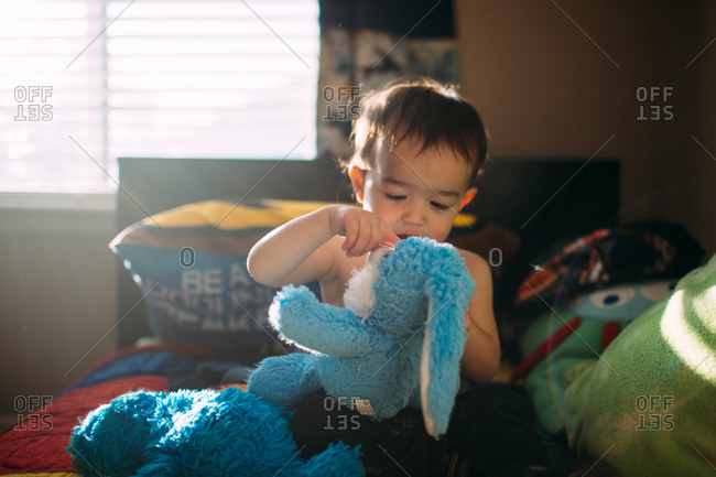 Toddler holding a doll on bed