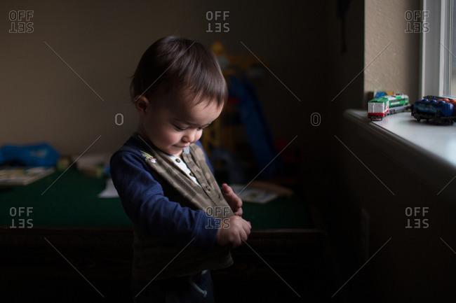 Toddler looking at his shirt