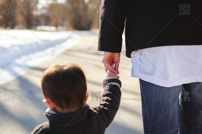Child holding adult's hand outside