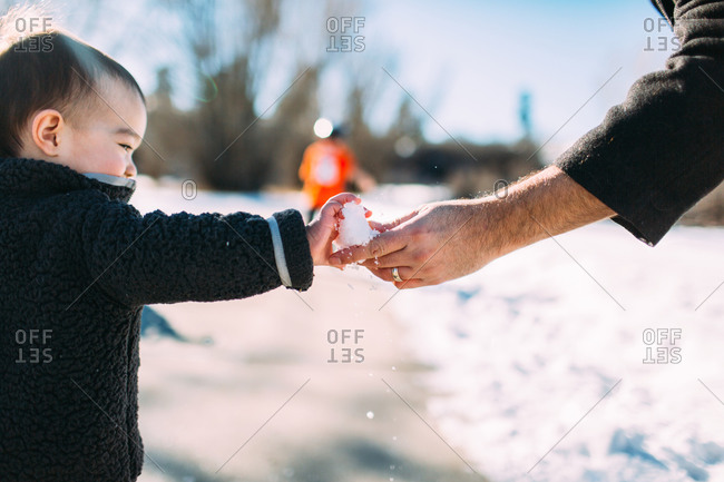 Child and man holding snow