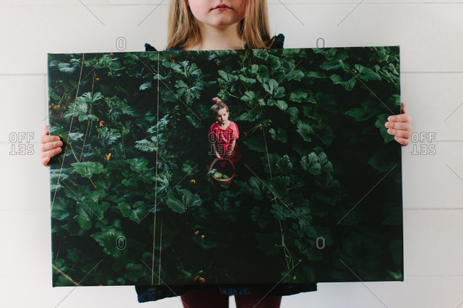 Girl holding canvas print of a girl in red dress standing in a pumpkin patch