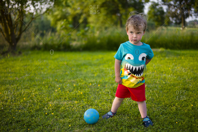 Portrait of toddler boy playing soccer on late afternoon