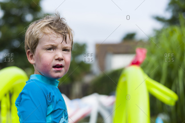 Young boy having fun in an inflatable swimming pool