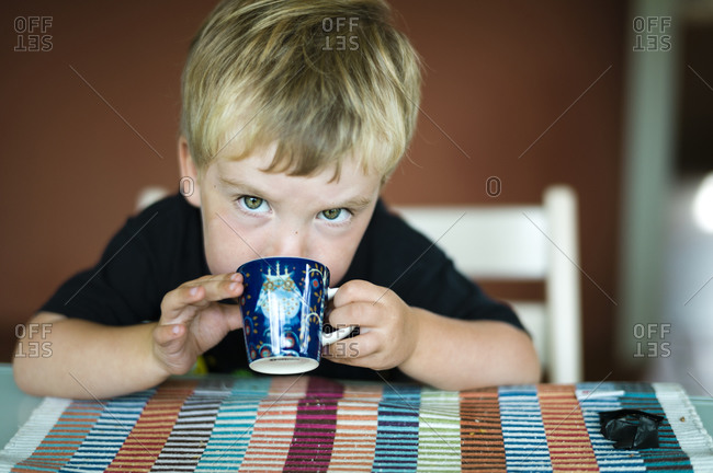 Portrait of young boy drinking from a small mug